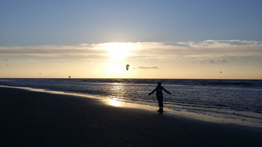 Sky Sunset Nature Water Sea Beach Land Beauty In Nature Horizon Over Water Horizon Real People Scenics - Nature Lifestyles Silhouette One Person Leisure Activity Full Length Animal Animal Themes Sun Kite Surfing Kite Kite Surfers