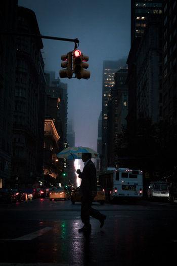 Man working on city street at night