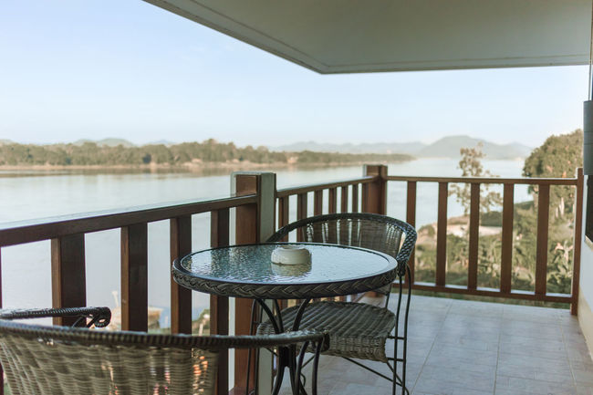 Mountain View Riverside Architecture Balcony Beauty In Nature Built Structure Chair Close-up Day Focus On Foreground Furniture Home Showcase Interior Nature No People Outdoors Place Setting Plate Railing Relax Peace Scenics Sea Sky Table Tree Water