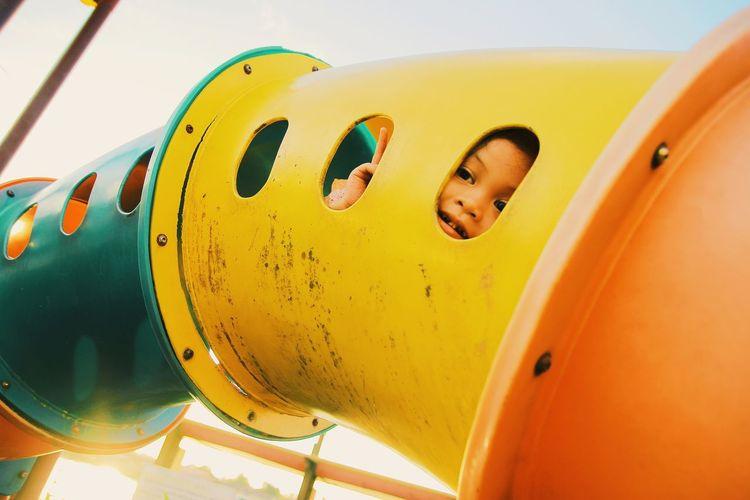 Cute boy looking through slide