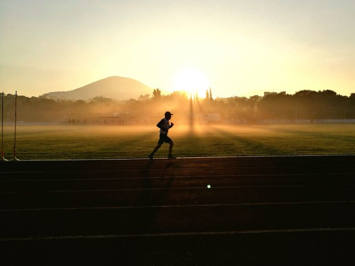 Man running on sports track against sky during sunset
