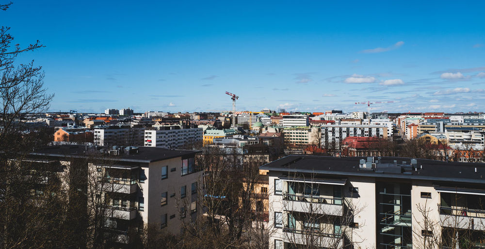 Scenic view of buildings in city against blue sky
