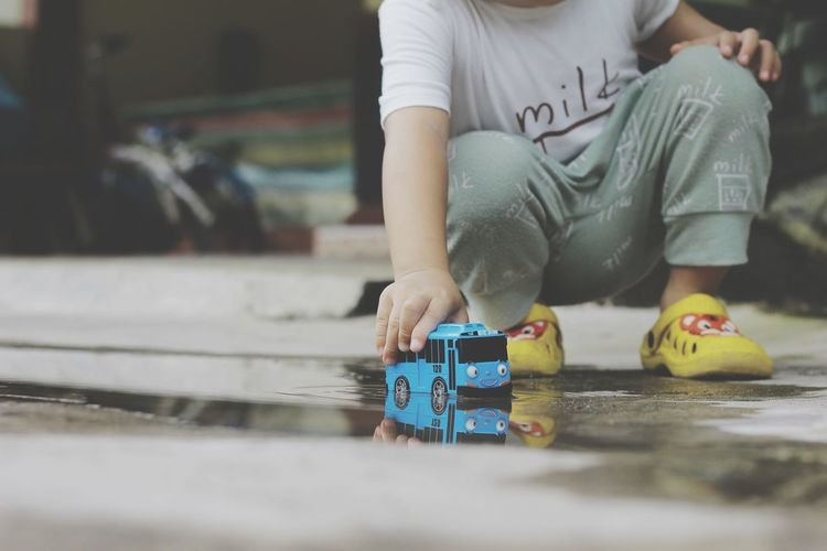 Low section of boy playing with toy car