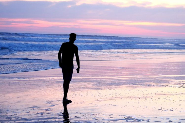 Solitary man on beach at sunrise