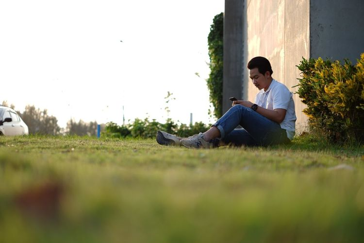 Casual Clothing Contemplation Day Field Full Length Grass Land Leisure Activity Lifestyles Nature One Person Outdoors Plant Real People Relaxation Resting Selective Focus Sitting Sky Surface Level Young Adult Young Men