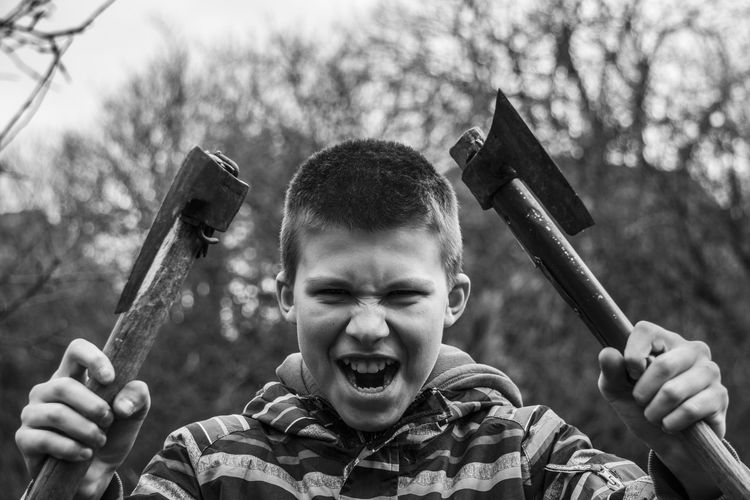Portrait of boy holding axes in forest