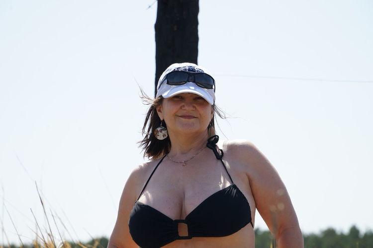 Portrait of sensuous woman in bikini top standing against clear sky