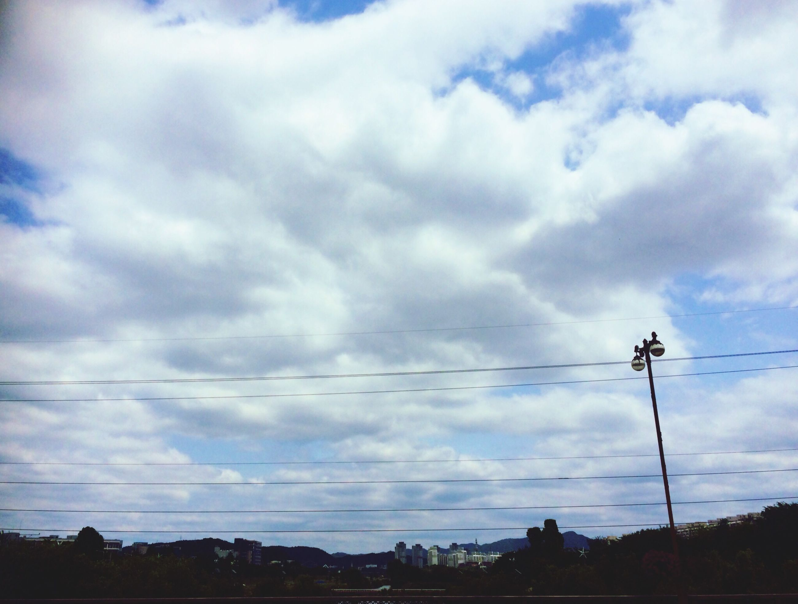 power line, electricity pylon, electricity, power supply, sky, cable, fuel and power generation, connection, low angle view, cloud - sky, cloudy, technology, power cable, cloud, silhouette, nature, outdoors, no people, telephone pole, tree