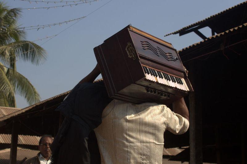 Rear View Of Man Carrying Harmonium