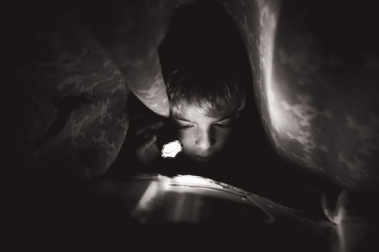 Boy reading book using flashlight in darkroom