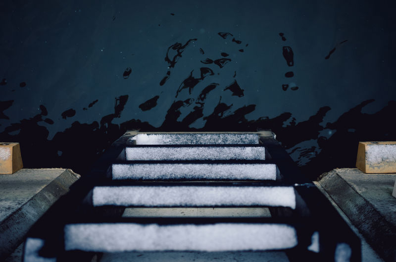 Top view of a ladder descending to water.