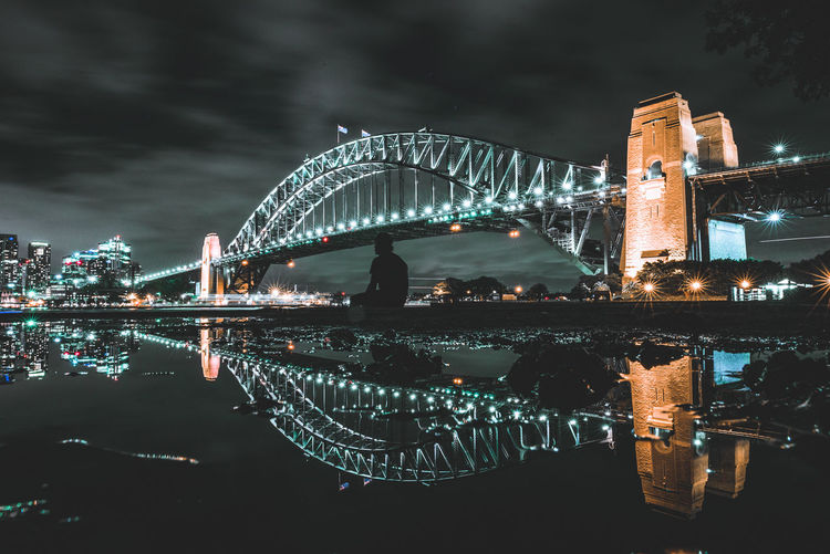 Illuminated bridge against sky at night
