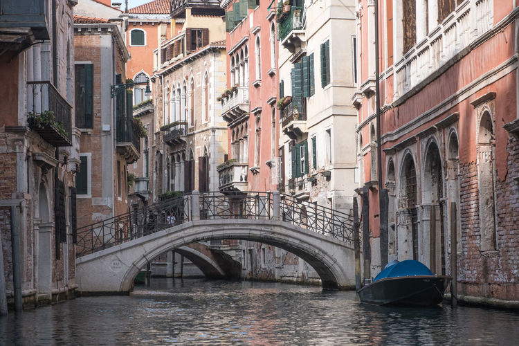 Bridge over canal by buildings in city