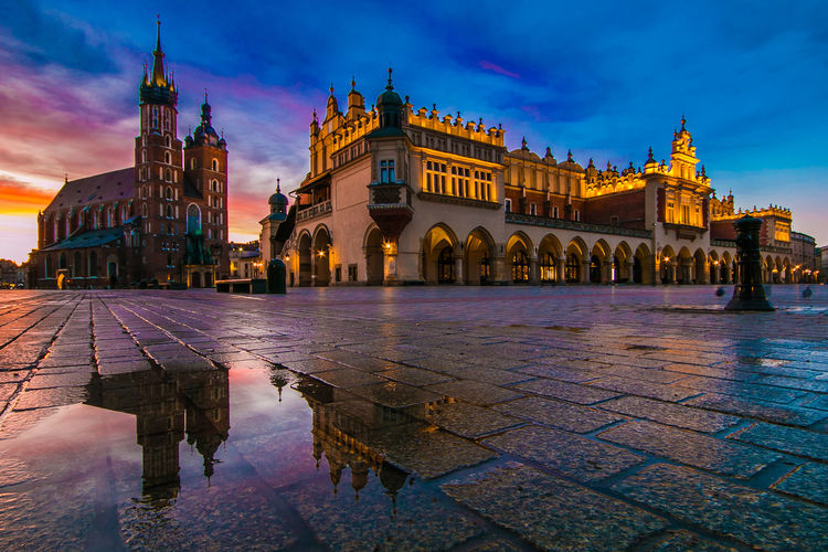Amazing and romantic view of Krakow medieval market square at sunrise with reflection in the puddle Krakow Kraków, Poland Poland Sunrise Sunrise_sunsets_aroundworld Sunrise_Collection Basilica Saint Mary Saint Mary's Cathedral Church Romantic Romantic Sky Market Square Medival Rynek Główny Arch Buildings Palace Center Urban Skyline Rainy Days Fantastic Card Wallpaper Travel Destinations Travel Vacation Winter Season  Famous Place Built Structure Architecture Building Exterior Sky City Illuminated History The Past Cloud - Sky Water Dusk Building Tourism Reflection Wet Rain Outdoors Rainy Season Nature