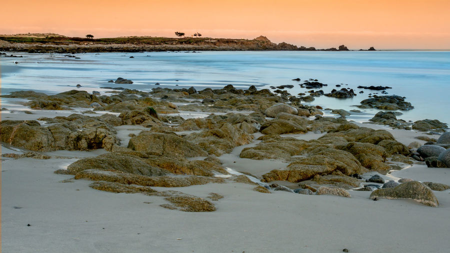 Long exposure landscape of the ocean near Pebble Beach, Monterey, California,, USA, on the 17-mile drive route in the winter of 2018, in the sunrise, featuring the rocks in the foreground Water Sea Sky Sunset Scenics - Nature Beauty In Nature Beach Rock Tranquility Nature Land Rock - Object Solid Tranquil Scene No People Horizon Over Water Horizon Idyllic Non-urban Scene Long Exposure Photography Landscape Pebble Beach Monterey Bay California USA 17-Mile Drive Sunrise Copy Space Over Ocean Rocky Beach With Sand