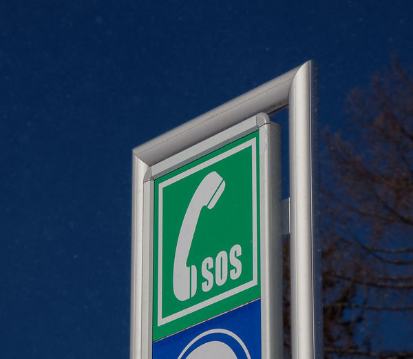 Close-up of sign against blue sky