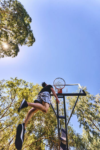 Low Angle View Of Man Putting Ball In Basketball Hoop Against Clear Sky