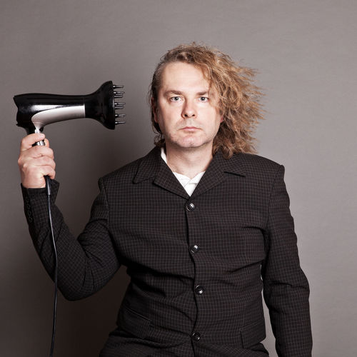 Portrait of man with hairdryer
