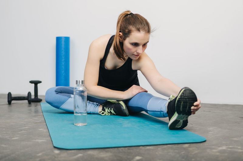 Young woman Stretching after workout in Gym Full Length One Person Young Women Sitting Young Adult Indoors  Front View Lifestyles Real People Women Casual Clothing Beauty Healthy Lifestyle Sport Hair Leisure Activity Exercising Hairstyle Beautiful Woman Fitness Workout Working Working Out Inside Photography Horizontal Sport Clothes Sport Clothing Athlete