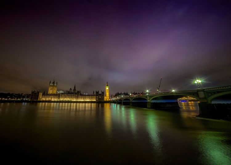 Westminster bridge by thames river against sky in city at night