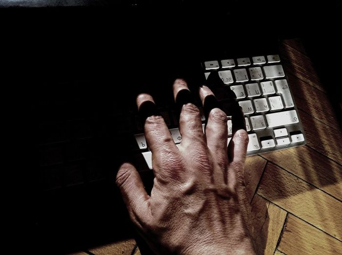 Close-up of hands using computer keyboard