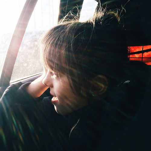 Close-up of girl looking through car window