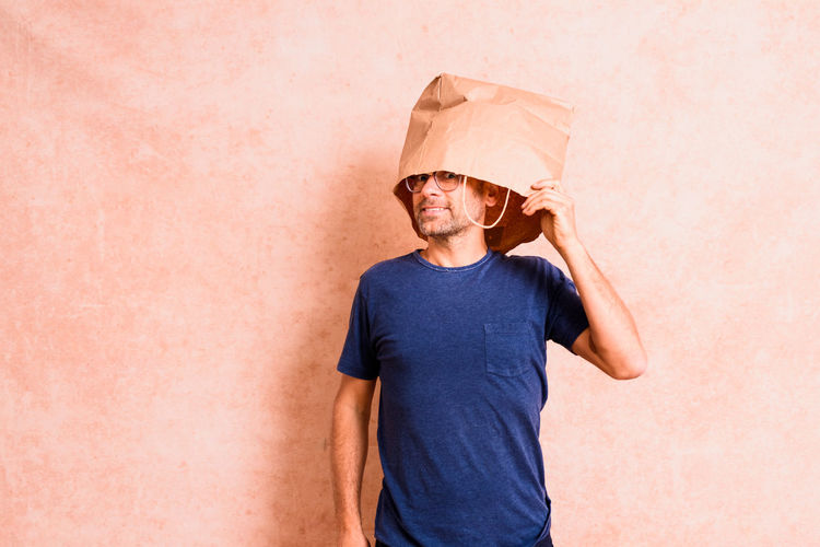 Man wearing hat standing against wall