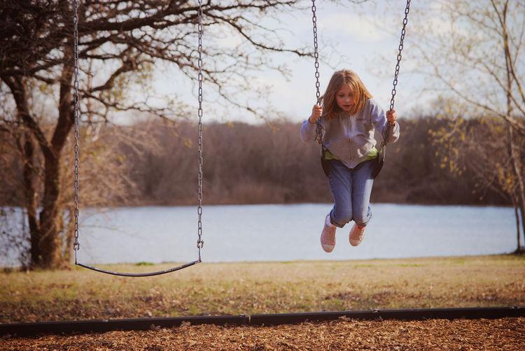 Girl swinging at lakeshore against sky
