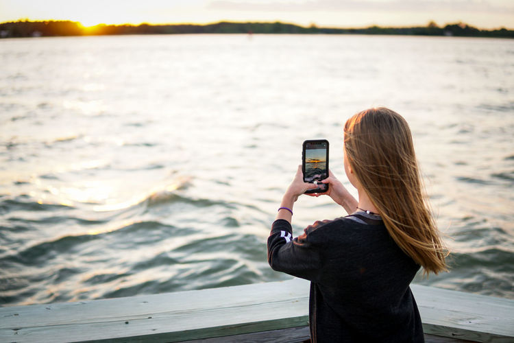 Woman photographing with mobile phone in sea