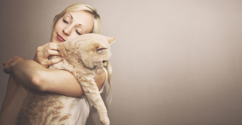 Beautiful woman holding cat against beige background