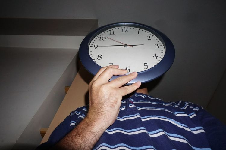 Low angle view of man holding clock while standing at home