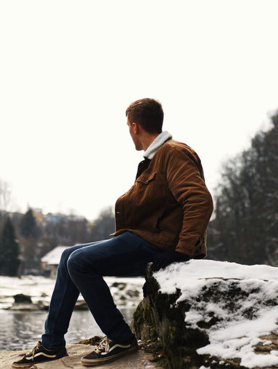 Side view of young man sitting on snow