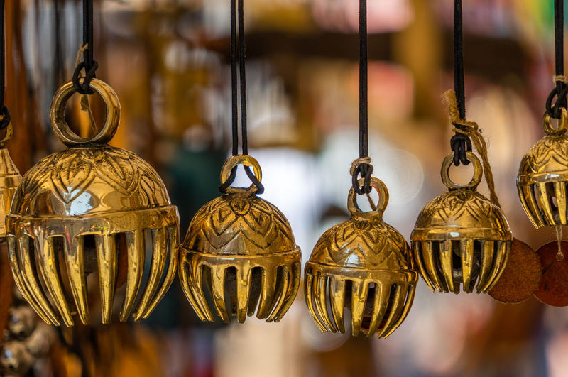 Small carillon and wind chimes made of copper, fake gold Hanging Art And Craft Focus On Foreground No People Choice Close-up Creativity Metal Gold Colored Variation Decoration Craft For Sale Group Of Objects Antique Indoors  Design Selective Focus Retail  Still Life Retail Display