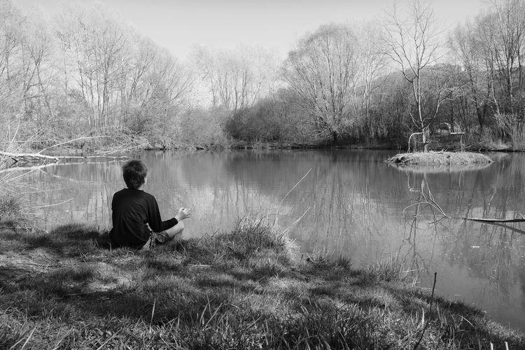 Rear view of boy sitting by lake