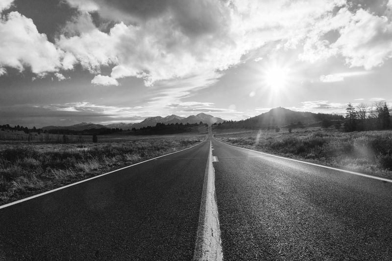 On The Road Driving The Way Forward Road Sky Lens Flare Cloud - Sky Nature No People Outdoors Landscape Sun Scenics Tranquility Tranquil Scene Transportation Beauty In Nature Sunlight Mountain Day Black And White Rural Poetry Rural Scene Road Minimalism