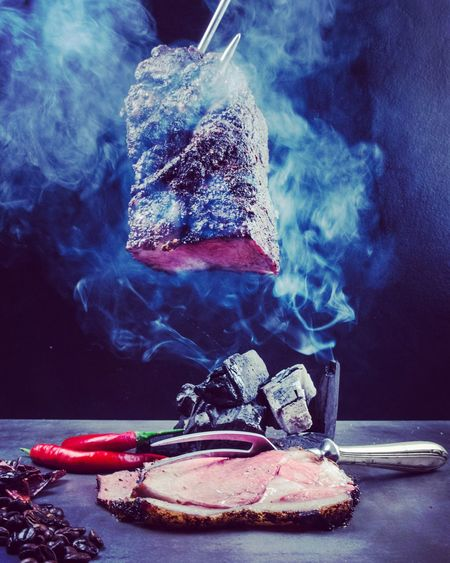 Smoke Emitting From Meat Against Black Background
