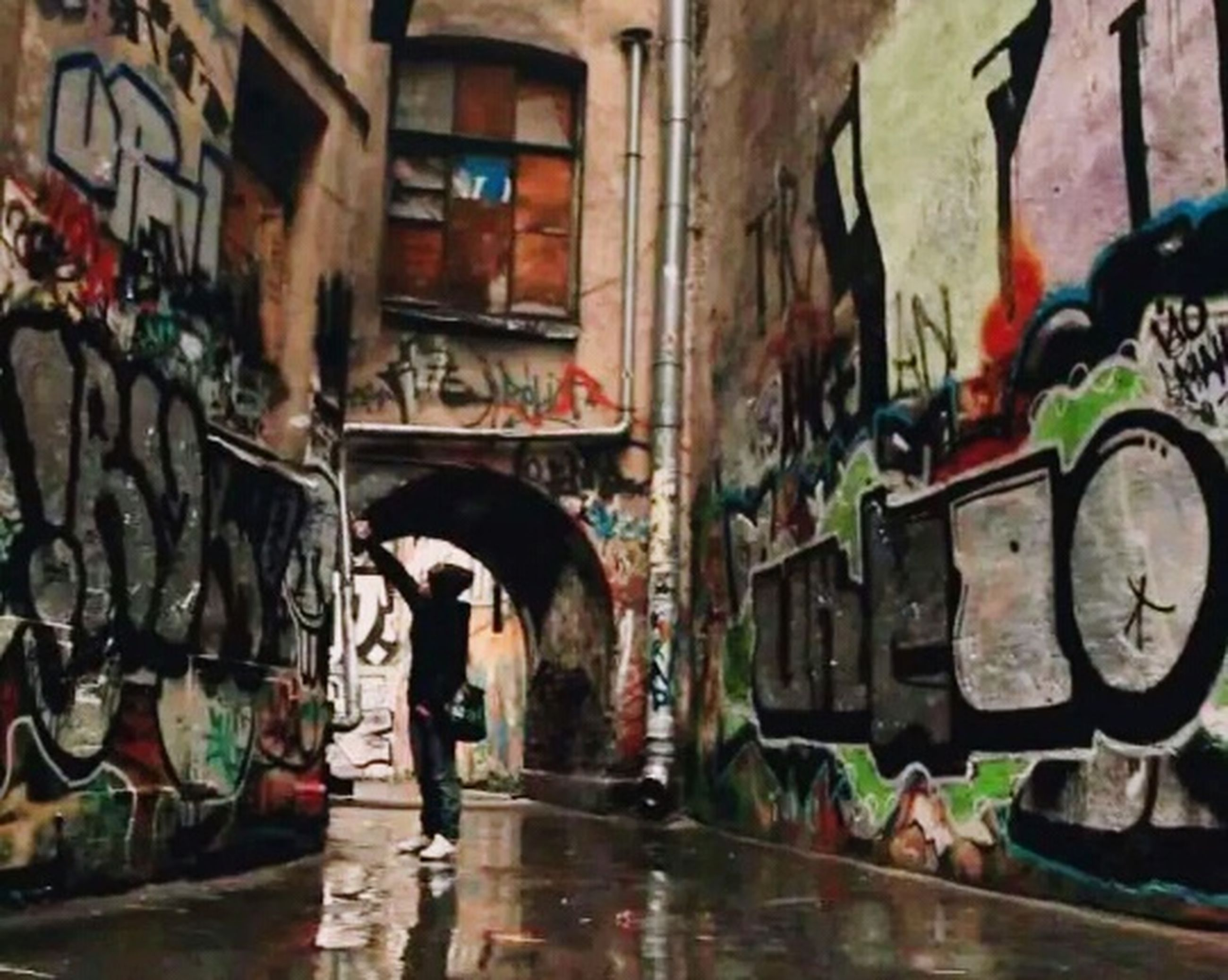 graffiti, architecture, built structure, building exterior, wall - building feature, lifestyles, street, men, wall, reflection, standing, full length, building, leisure activity, window, day, indoors