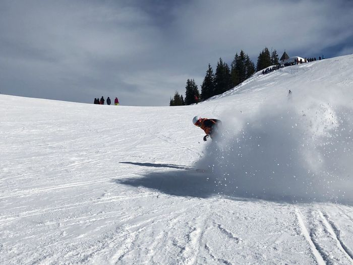 Teenage boy skiing on snow covered landscape against sky