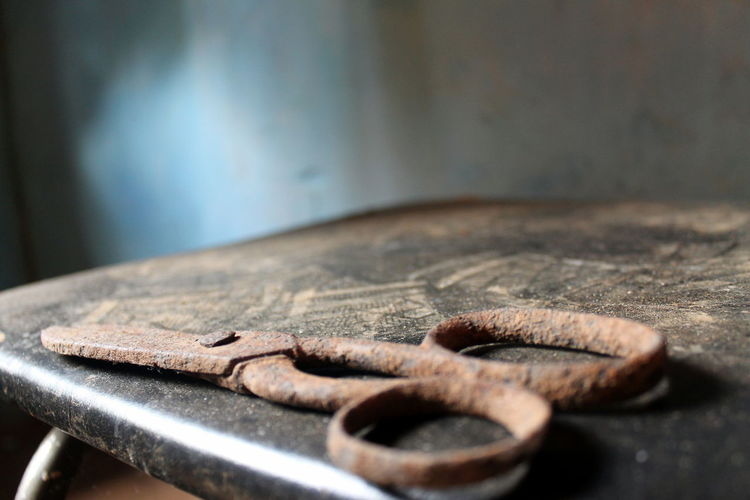 Close-Up Of Old Rusty Scissor On Table