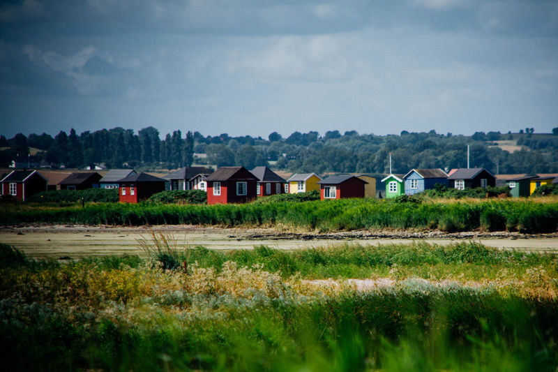 Huts on landscape against sky