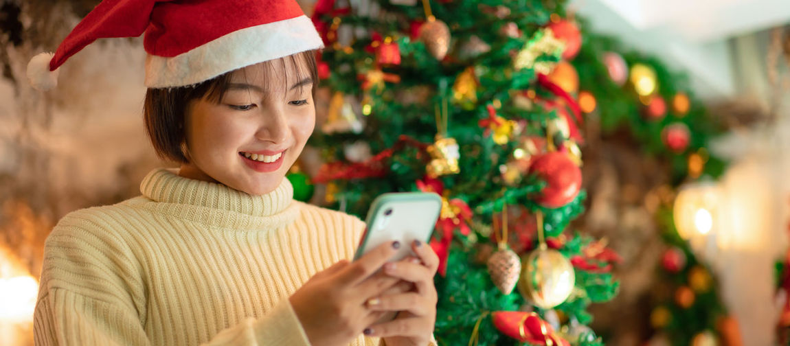 Portrait of smiling young woman holding christmas tree