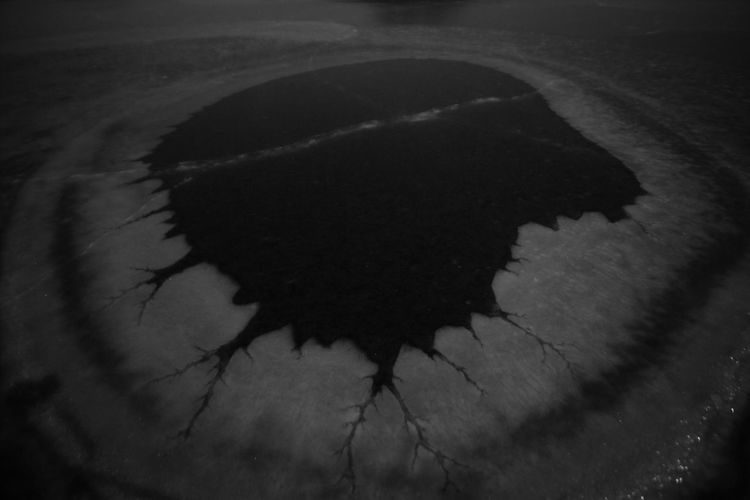 High angle view of black reflection in puddle