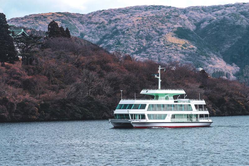 Nautical vessel on sea against mountains