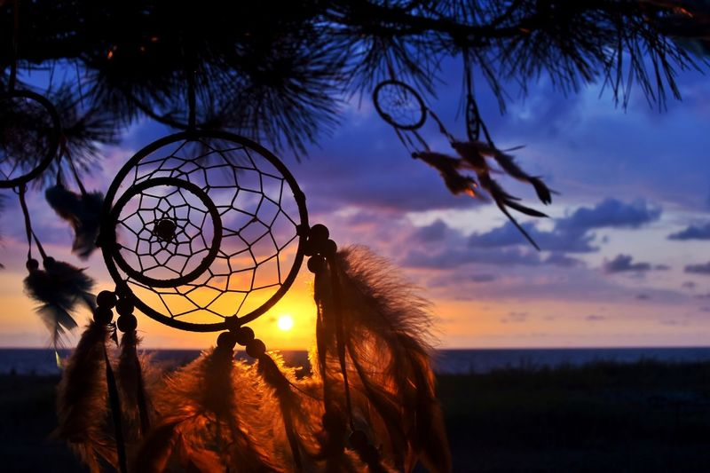 Close-up of dreamcatcher against sky during sunset