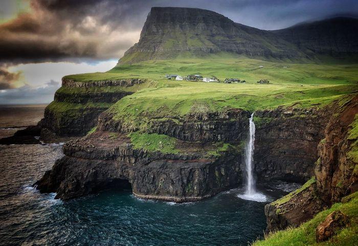 Gasadalur waterfall in Faroe Faroe Island Gasadalur Waterfall Scenics - Nature Beauty In Nature Water Land Tranquil Scene Sky Tranquility Nature Cloud - Sky Environment Mountain Green Color Landscape Flowing Water Solid Rock Idyllic Non-urban Scene No People Day
