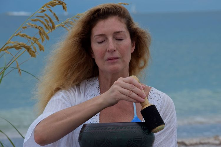 Woman meditating with singing bowl with wooden striker at beach