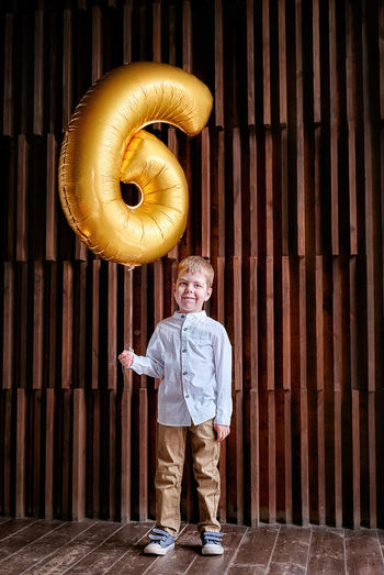 Portrait of boy holding 6 number balloon