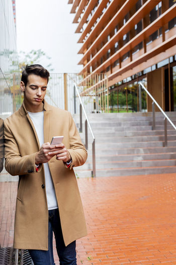 Young Man Using Phone While Standing By Wall