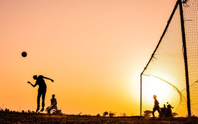 Silhouette friends playing soccer against sky during sunset