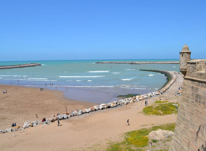 A beautiful beach overlooking Sale in Rabat Morocco, 2013 Land Nature Day Outdoors Beach Rabat Rabat Morocco Old Castle 2013 Sea Water Sky Horizon Over Water Horizon Clear Sky Blue Group Of People Scenics - Nature Travel Beauty In Nature Copy Space High Angle View Architecture Large Group Of People